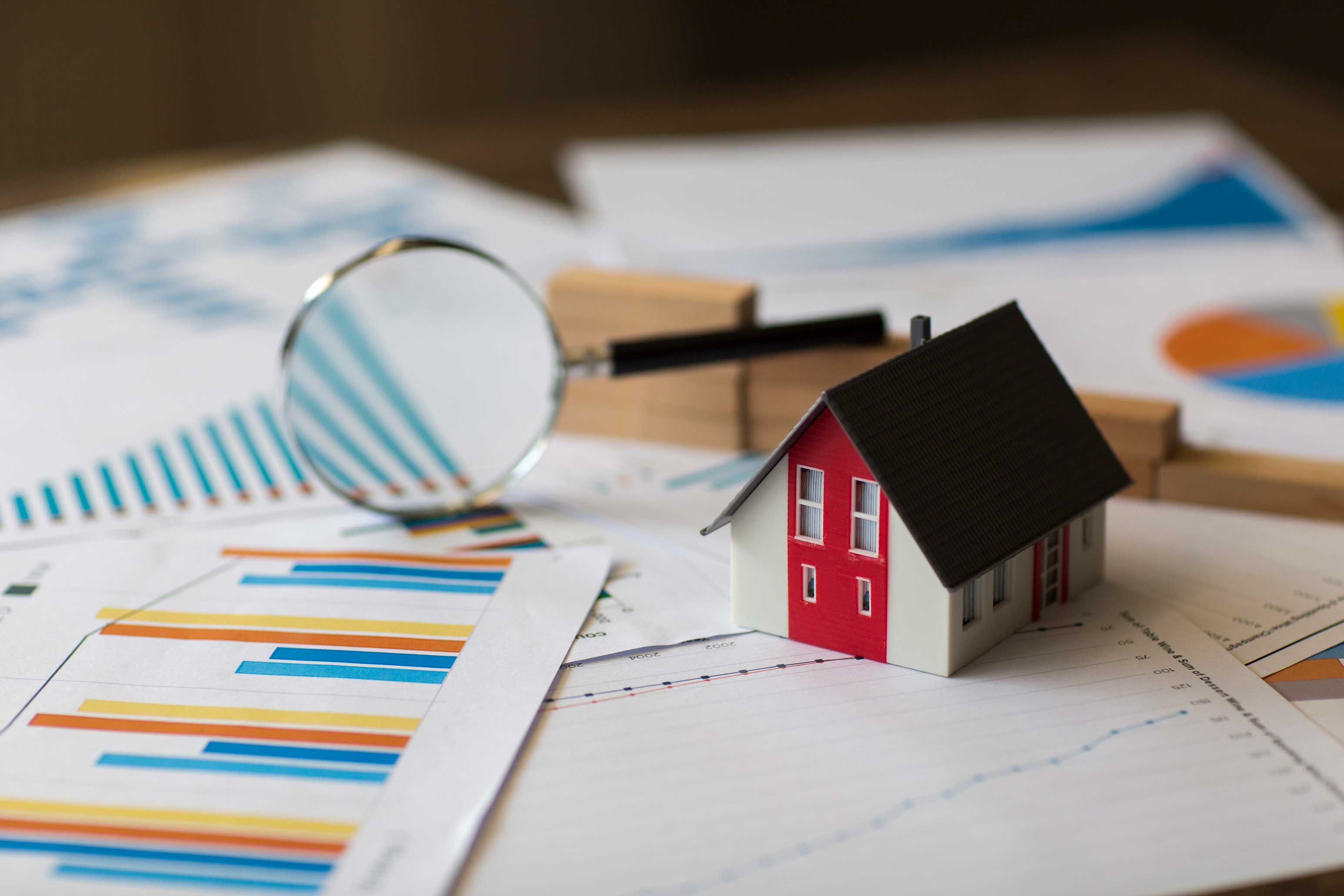 Photo of a miniature house on a set of papers with financial graphs and a magnifying glass in the background