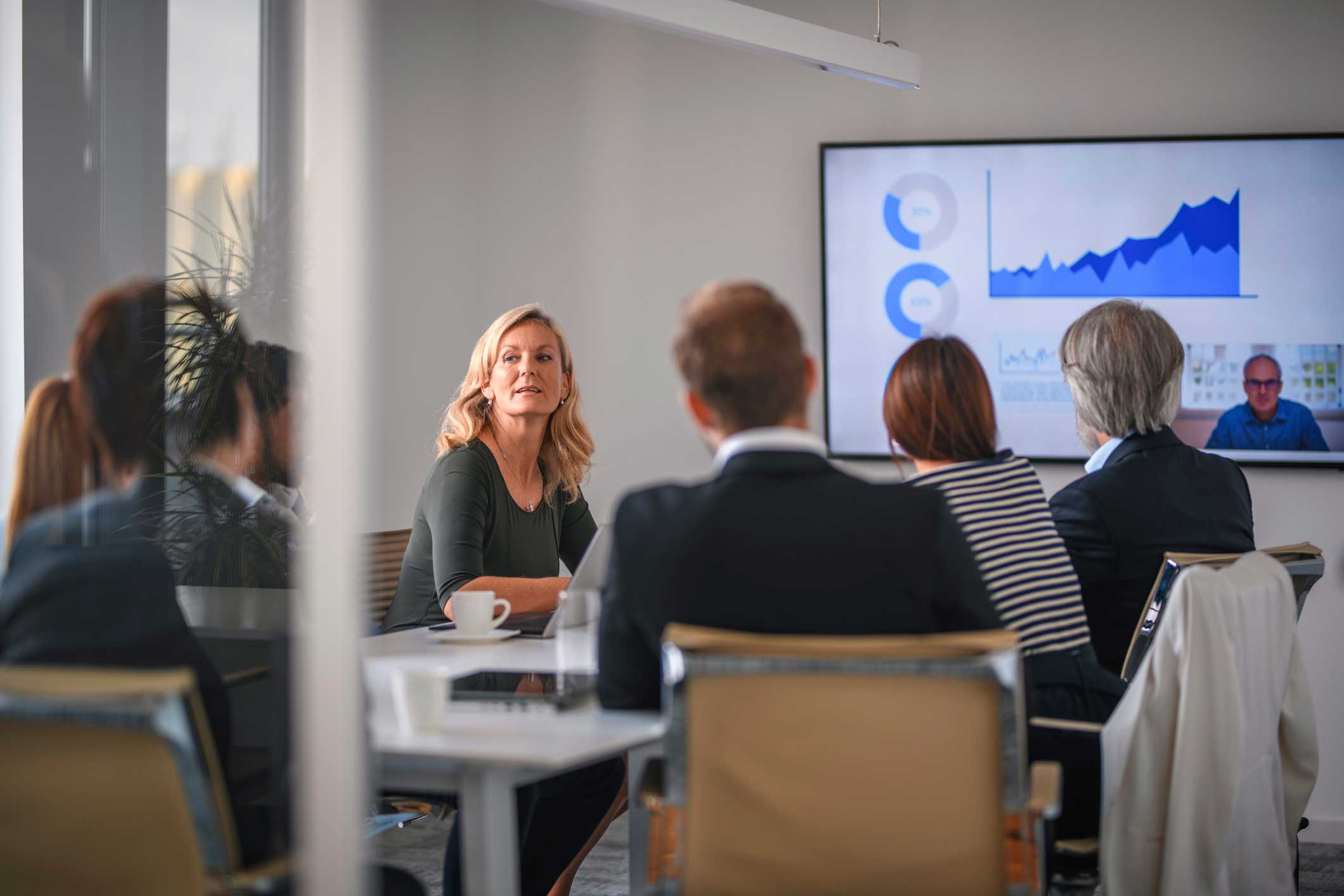 Employees around a conference table discussing a presentation with a client on screen for a video conference
